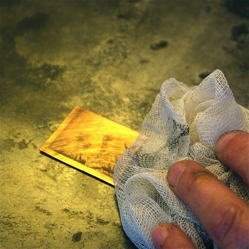 Main d'un graveur en train de nettoyer une plaque de métal gravée